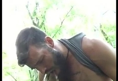 Hairy dude pissing on himself in the forest